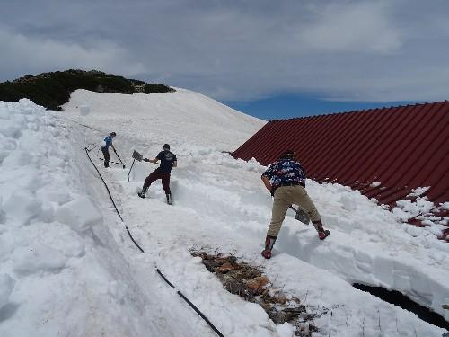 """03537<br /> """" class=""""alignnone"""" /></div> <p>この陽気で午前中から除雪作業や布団干し。長靴履いてのこの時期の除雪作業は、体全体が汗ばみます。ちなみに、この除雪場所は本館の屋根。木造の建物ゆえ、真上からの雪の重みはなんとか凌げても、横から加わる重みには弱い、つまり今本館の建物は、歪んでいる状態で、それを何とか一日も早く解消してあげなくてはなりません。<br /> しかし、この汗ばむ陽気も手伝って、何とか屋根の際を全て出すことができたので、とりあえず一安心。この屋根の上に乗っかっている雪も無くなれば、小屋は徐々に起き上り、館内の開かない扉等が開くようになってくるんです。</p> <p>さて明日はヘリコプターの空輸作業。今のところ明日も梅雨の中休み続きそうです。</p> <p> 無事フライトなることを願いつつ、除雪での心地よい疲れを癒す、""""缶ビール""""で一杯といきましょうか・・・</p> <nav class="""